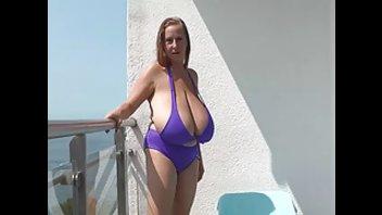 Дамочка с невероятно большой грудью позирует топлес перед камерой